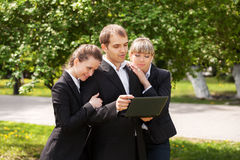 Young business people using laptop in a city park Stock Photos