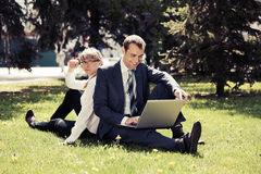 Young business people using laptop in a city park Stock Photo