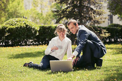 Young business people using laptop in a city park Royalty Free Stock Photos