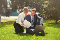 Young business people using laptop in city park Royalty Free Stock Images