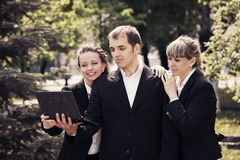 Young business people using laptop in a city park Stock Images