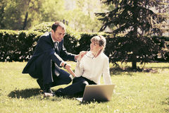 Young business people using laptop in a park Stock Photography