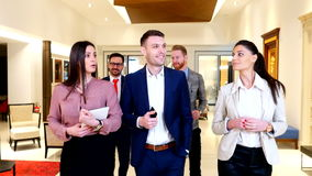 Young business people walking in modern office stock video