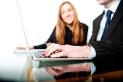 Young business people working on laptop together Royalty Free Stock Image