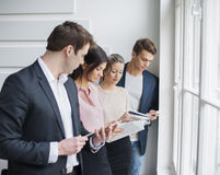 Young business people working by window in office Stock Images