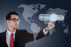 Young business person with start button Stock Images