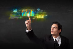 Young business person touching colorful charts and diagrams stock photography