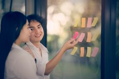 Young business persons are discussing with happiness. And put sticky note on the glass windows Stock Image
