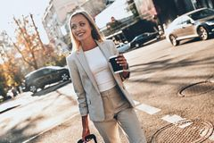 Young business professional. Beautiful young woman in suit pulling luggage and smiling while walking outdoors stock photos