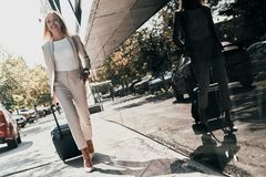 Young business professional. Full length of young woman in suit pulling luggage and smiling while walking outdoors stock photos