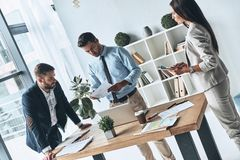 Young business professionals. Group of young modern people in smart casual wear discussing business while standing in the creative office royalty free stock photography
