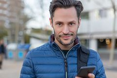 Young business smiling man in the street with a cellphone and a blue jacket royalty free stock image