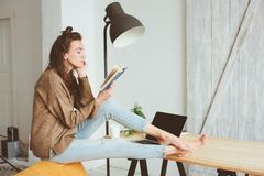 Young business or student woman working at home with laptop. And reading book royalty free stock photos