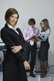 Young business team. Smiling business woman in office at her collegues background Stock Photos
