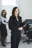 Young business team. Smiling business woman in office at her collegues background Royalty Free Stock Photos