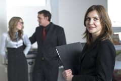 Young business team. Smiling business woman in office at her collegues background Stock Images