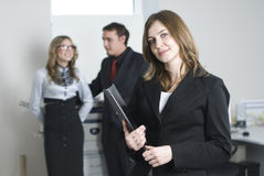 Young business team. Smiling business woman in office at her collegues background Royalty Free Stock Photography