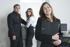 Young business team. Smiling business woman in office at her collegues background Royalty Free Stock Photo