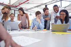 Young business team gathered around two laptops in an office stock photography
