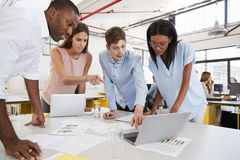 Young business team work standing at desk in a busy office Royalty Free Stock Image