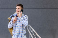 Young business traveler using cell phone. Outdoors. Talking over smart phone Royalty Free Stock Image