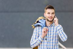 Young business traveler using cell phone. Outdoors. Talking over smart phone Stock Photo