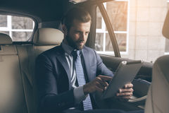 Young business using digital device. Young business person test drive new vehicle using digital device Stock Photos
