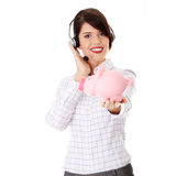 Young business woman. With headset holding piggy bank Stock Photography