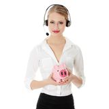 Young business woman. With headset holding piggy bank Stock Photo