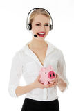 Young business woman. With headset holding piggy bank Royalty Free Stock Photos