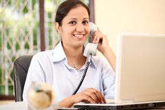 Young business woman. Cheerful business woman talking on phone royalty free stock photography