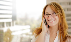 Young Business woman. Young red hair business woman is  on the phone and smiling while doing business Royalty Free Stock Image