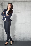 Portrait of a beautiful businesswoman standing against grunge background Royalty Free Stock Image