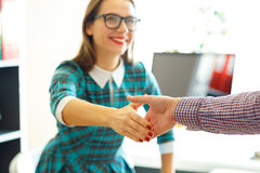 Young business woman with arm extended to handshake Stock Photos