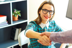 Young business woman with arm extended to handshake Royalty Free Stock Photography