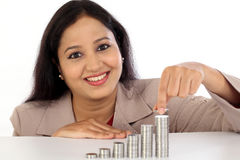 Young business woman arranging stack of coins Stock Photography