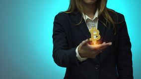 Young business woman with bitcoin crypto currency in hand. In studio on blue background stock footage