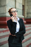 Young business woman in black suit and glasses talking on phone Royalty Free Stock Image
