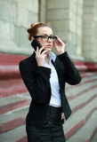 Young business woman in black suit and glasses talking on phone Stock Photo