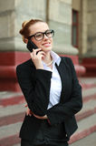 Young business woman in black suit and glasses talking on phone Stock Photos