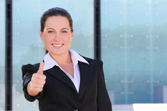 Young business woman in black suit thumbs up Stock Photo