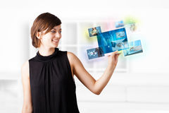 Young woman browsing pictures on modern tablet Stock Photos