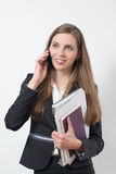 Young business woman busy with a laptop and papers speaking on the phone Royalty Free Stock Image