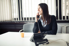 Young business woman calling and communicating with partners.Customer service representative on the phone. Cheerful secretary answering phone in her office and Royalty Free Stock Photography