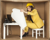 Young business woman carefully reading building plans Royalty Free Stock Photography