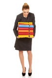Young business woman carries heavy binders Royalty Free Stock Photography