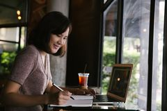 Young business woman in casual dress sitting at table in cafe and writing in notebook stock photos