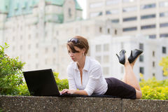Young business woman casualy works on laptop in the city Royalty Free Stock Photo