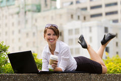 Young business woman casualy works on laptop in the city Royalty Free Stock Image