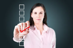 Young business woman checking on checklist box. Stock Images